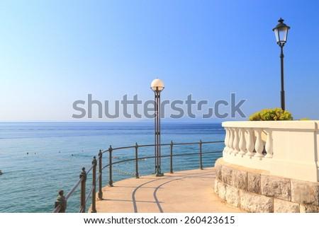 Street lamps on sunny alley on the promenade above Adriatic sea, Opatija, Croatia - stock photo