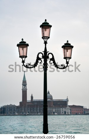 Street lantern on quay of Venice in cloudy weather