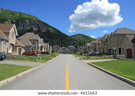 Street leading to the mountain in a rich suburban neighborhood. - stock photo
