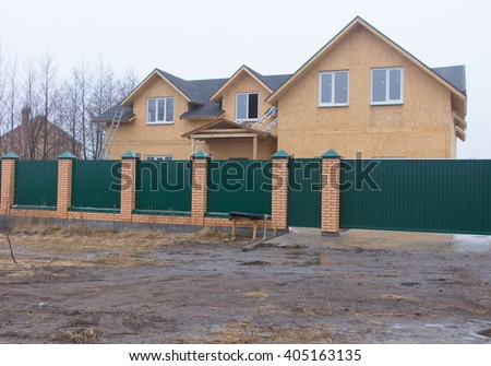 Street level view on single two story house without exterior finishing under construction behind thick green and brick fence during winter - stock photo