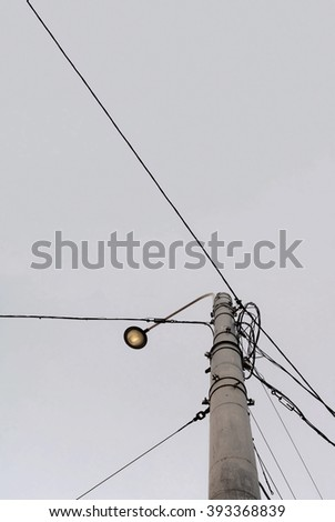 Street light and electrical wires against sky background