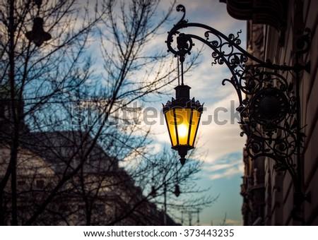 Street light at sunset in Budapest, Hungary, Europe. Yellow light of lamp against blue sunset sky. - stock photo