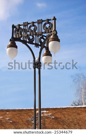 Street light in winter time with blue cloudy sky as background - stock photo