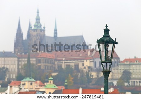 Street light on traditional cast iron pole on the Charles bridge with Gothic church and castle in the background, Prague, Czech Republic - stock photo