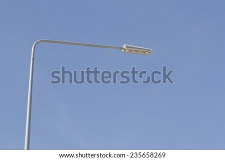 Street light pole on blue sky - stock photo