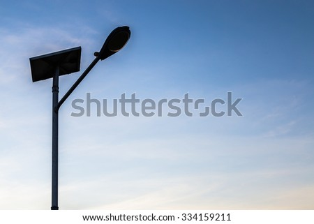Street light powered by solar energy. Solar panel and LED lamp. Silhouette of a street lamp. - stock photo