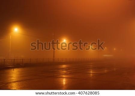 Street lights, foggy misty night, lamp post lanterns, deserted road in mist fog, wet asphalt and tram - stock photo