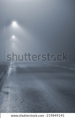 Street lights, foggy misty night, lamp post lanterns, deserted road in mist fog, wet asphalt tarmac, car headlights approaching, blue key  - stock photo