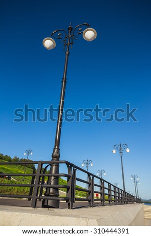 Street lights on the promenade on the shore of the great river - stock photo