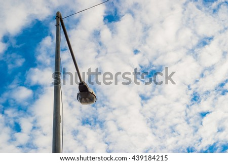 Street lights with arrow against blue sky background.