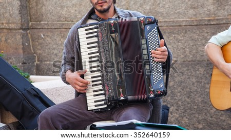 Street musician playing accordion in Milan, Italy - stock photo