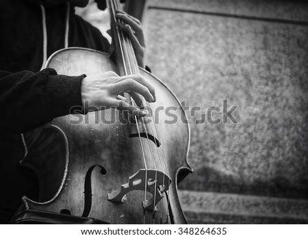 Street musician's hands playing bass on an acoustic instrument in urban environment in winter.
