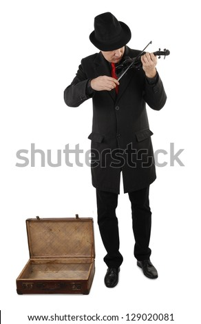 Street musician with violin and open old suitcase - stock photo