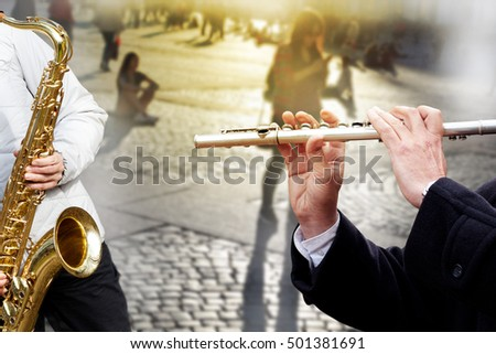Street musicians. They play in the square. Saxophone and flute.