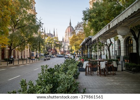 Street of Budapest with a pavement cafe and a view at the Hungarian Parliament Building on a bright autumn day