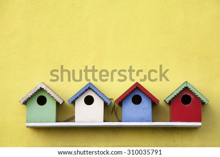 Street of four colorful birdhouses hanging on a yellow wall - stock photo