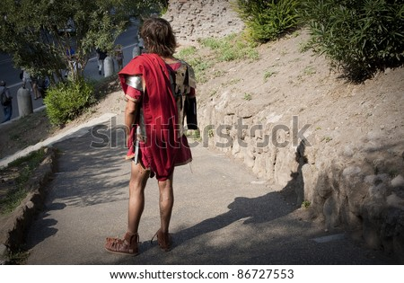 Street performer dressed like Roman soldier offer photo sessions to tourists in a park near Colosseum, Rome.