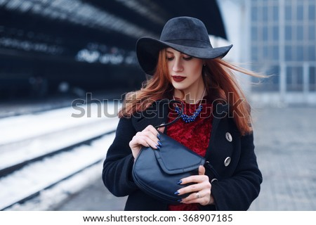 Street portrait of a young beautiful elegant redhead woman holding dark blue leather handbag. Lady wearing stylish clothes. Female fashion concept. Closeup - stock photo