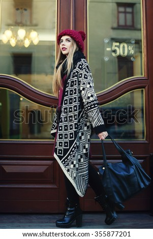 Street portrait of fashionable beautiful young woman entering shop. Lady wearing stylish winter clothes. Female fashion concept.  - stock photo
