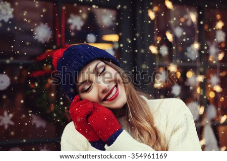 Street portrait of smiling beautiful young woman with closed eyes.  Lady wearing stylish classic winter knitted woolen clothes. Festive  garland lights. Magic snowfall effect. Close up. Toned - stock photo
