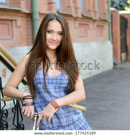street portrait of young beautiful woman with bicycle