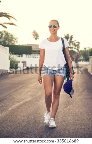 Street portrait of young, tanned polish woman. Girl coming back, walking towards the camera. Copy space around the girl. - stock photo