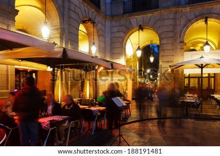 Street restaurants at Placa Reial in winter evening. Barcelona - stock photo