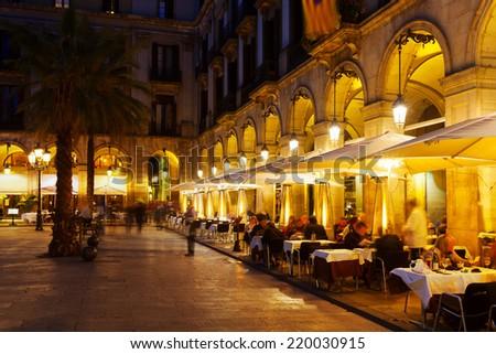 Street restaurants at Placa Reial in winter evening. Barcelona, Spain - stock photo