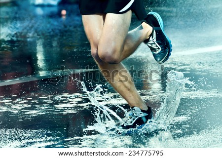 Street runner runs through a puddle - stock photo