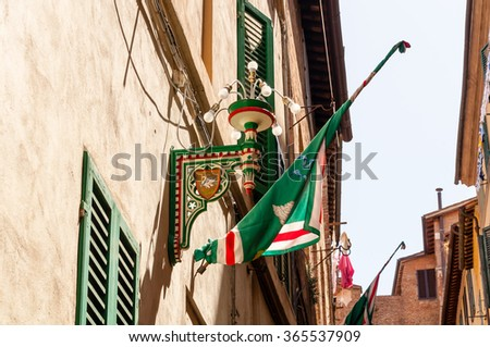 street scene in siena with flags of the contrada of the goose - stock photo