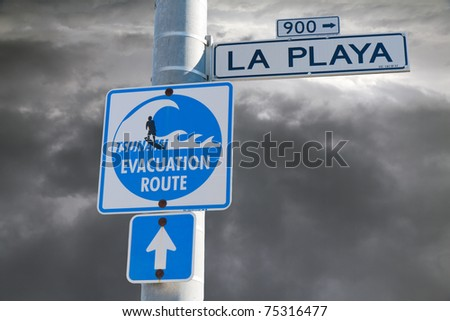 street sign at the beach pointing out the tsunami evacuation route, isolated - stock photo