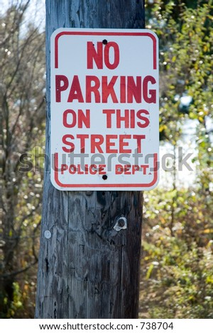 "Street Sign which reads in bright red letters: ""NO PARKING ON THIS STREET Police Dept."" on a telephone poll.  Shallow focus."