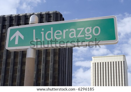 "Street sign with an arrow and the Spanish word ""liderazgo"" located in a business district - stock photo"