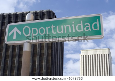 "Street sign with an arrow and the Spanish word ""oportunidad"" located in a business district - stock photo"