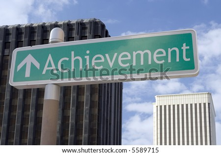 "Street sign with an arrow and the word ""achievement"" located in a business district. - stock photo"