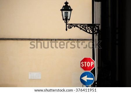 Street signs and light against pale yellow wall with dark shadows to right - stock photo