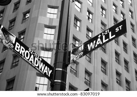Street signs indicating the intersection of Wall Street and Broadway. - stock photo