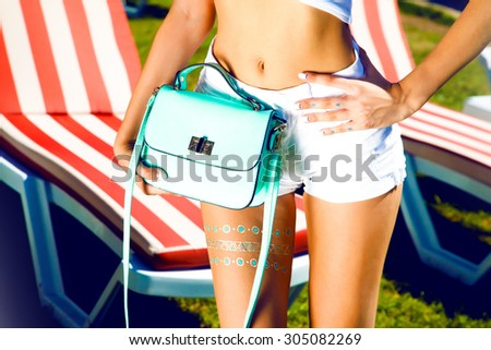Street style fashion details,bright blue romper,elegant white clothes,backpack and trendy jewelry,posing on the street,bright colors.clutch,bright handbag,advertises bags.luxury,party clothes - stock photo
