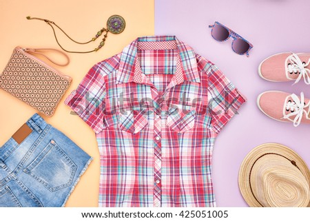 Street style Fashion girl clothes accessories set. Hipster woman, trendy handbag, plaid shirt, denim, gumshoes, hat necklace and sunglasses. Urban creative outfit.Overhead, top view on pink background - stock photo