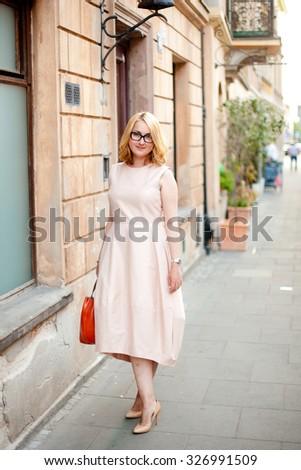 Street style, woman wearing elegant dress and heels. Narrow street of Warsaw. Poland  - stock photo