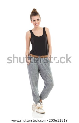 Street style. Young woman in gray track-suit, black top. Full length studio shot isolated on white. - stock photo