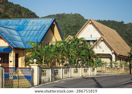 Street Thai village at the foot of green mountains - stock photo