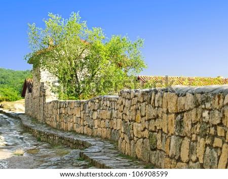 Street to the sidewalk in the ancient mountain village. Karaite culture. Crimea. - stock photo