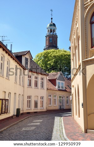 Street view at houses and a church tower of Leer, Germany