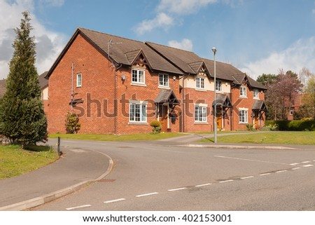 Street view of a typical mix of mid price range detached modern residential housing development in the United Kingdom - stock photo