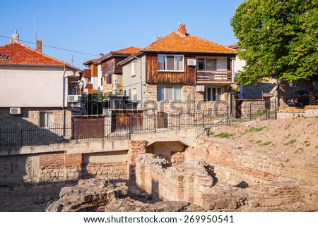 Street view of Nesebar, Bulgaria. Typical revival houses and ancient Roman ruins in the old town - stock photo