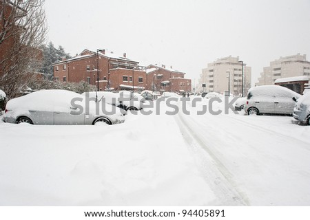 Street view with cars buried by the snow.