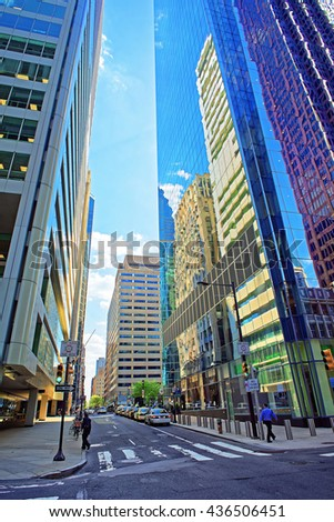 Street view with skyscrapers reflected in glass in the City Center of Philadelphia, Pennsylvania, USA. It is central business district in Philadelphia. Tourists in the street - stock photo