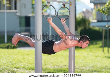 Street Workout - Handsome Muscular Man Workout In The Park - stock photo