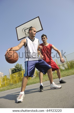 streetball basketball game with two young player at early morning on city court - stock photo